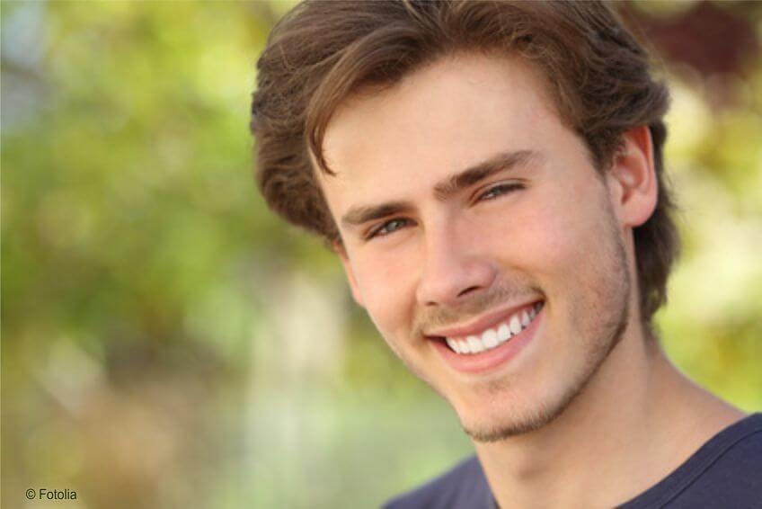 Lächelnder junger Mann mit weißen Zähnen auf www.weissezaehnebleaching.de